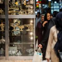Women pass a store display of glassware while shopping in the Grand Bazaar in Tehran on Monday. Iran's central bank, acting on the eve of U.S. sanctions, scrapped most currency controls introduced this year in a bid to halt a plunge in the rial that has stirred protests against the government of President Hassan Rouhani.   BLOOMBERG