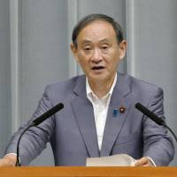 Chief Cabinet Secretary Yoshihide Suga speaks during a regular news conference at the Prime Minister's Office in this photo taken in August. On Tuesday Suga said mobile phone operators could cut phone bills by about 40 percent, pushing down the stock prices of those firms. | KYODO