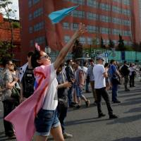 A youth releases a paper plane, symbol of the Telegram messenger, during a rally in against a court decision to block the messenger because it violated Russian regulations, in Moscow May 13. | TATYANA MAKEYEVA / VIA REUTERS