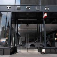 A woman walks past a Tesla showroom in Washington on Aug. 8. Tesla CEO Elon Musk disclosed on Monday he was in talks with Saudi Arabia's sovereign wealth fund and other investors to take the electric automaker private.   AFP-JIJI
