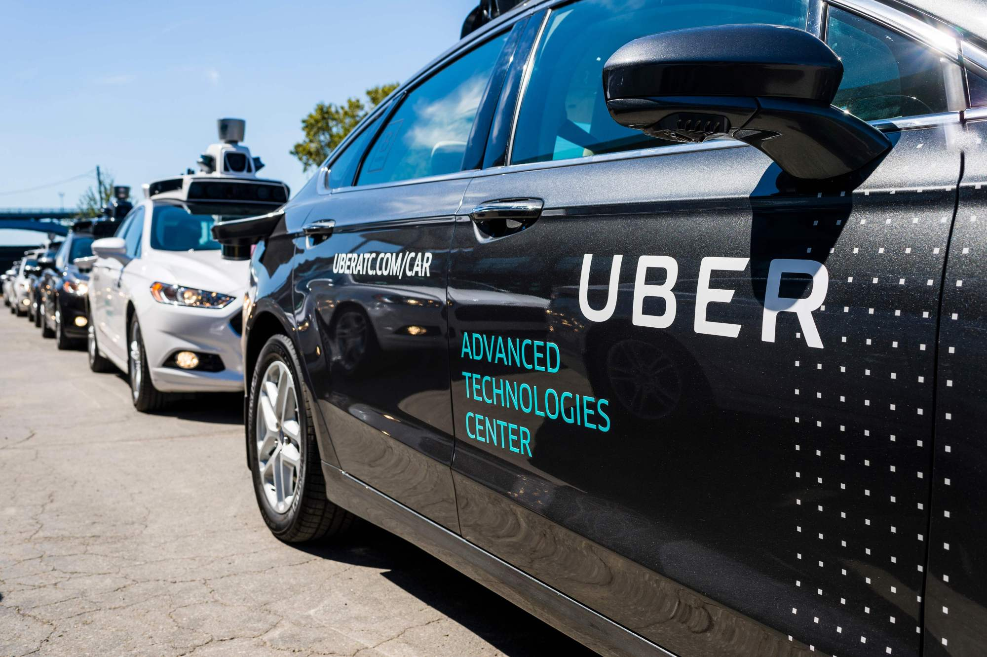Pilot models of the Uber self-driving car are displayed at the Uber Advanced Technologies Center in Pittsburgh, Pennsylvania in September 2016. Toyota will pump about $500 million into the ride-hailing giant as part of a deal to work together on mass-producing self-driving vehicles, the carmaker said Tuesday. | AFP-JIJI