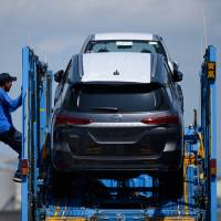 A worker prepares to unload Toyotas from a car carrier at Nagoya Port on July 31. Japan fell into red ink in goods trade for the first time in two months in July as the cost of energy imports surged. | BLOOMBERG