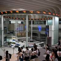 College students visit the Tokyo Stock Exchange on Friday, when the Nikkei index closed flat over global trade frictions and ahead of the release of key jobs data. | AFP-JIJI