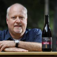 Kirk Duke, whose family runs a Napa Valley winery called Duke's Folly, poses with bottles of wine at his home in Falmouth, Maine, in July. The business was recently blocked from getting a trademark after Duke University intervened, saying it would lead to confusion with the school. Rather than risk a costly legal battle, the family agreed to a settlement requiring it to drop the trademark claim and tweak the name of the company, to Dukes' Folly. | ROBERT F. BUKATY / VIA AP