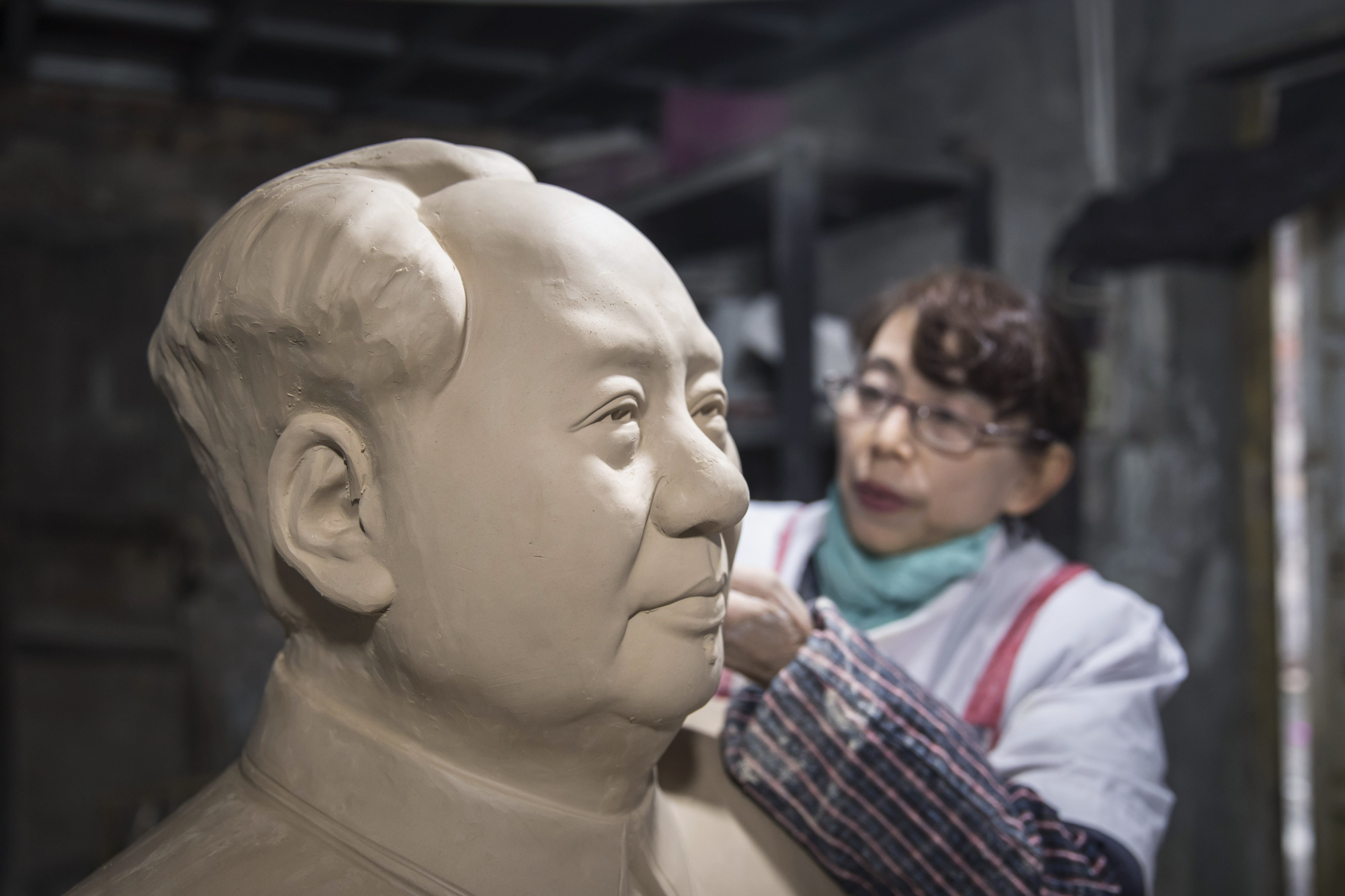 A worker sculpts a bust of former Chinese leader Mao Zedong inside a workshop at the Jingdezhen Porcelain Factory in Jingdezhen in China's Jiangxi province in January. | BLOOMBERG