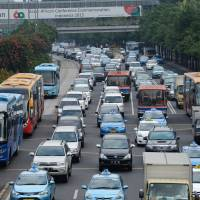 Vehicles jam a road during the morning rush hour in Jakarta. Yamaguchi Wrecker Co. of Japan is providing tow trucks to local authorities in Indonesia to help them remove illegally parked vehicles. | BLOOMBERG