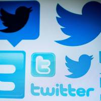 Twitter logos are seen on a computer screen in Beijing. Twitter on Thursday started requiring those behind hot-button issue ads in the U.S. to be vetted as part of the effort by the social network to thwart stealth campaigns aimed at influencing politics. | AFP-JIJI