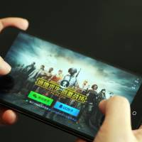 A mobile gamer plays Tencent's multiplayer online game 'PlayerUnknown's Battlegrounds' on his smartphone in Ji'nan city, Shandong province, on March 16. Tencent operates the world's largest games business by revenue thanks to its position in China, which according to data from consultancy Newzoo is the world's top video-games market with an estimated revenue of $37.9 billion. | IMAGINECHINA / VIA AP