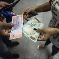 People display the new 2 and 5 sovereign bolivar banknotes for a photograph after withdrawing from automated teller machines (ATM) in Caracas on Monday. The Venezuelan government is re-denominating the bolivar currency by lopping off five zeroes, this as it carried out one of the greatest currency devaluations in history over the weekend. | CARLOS BECERRA / VIA BLOOMBERG