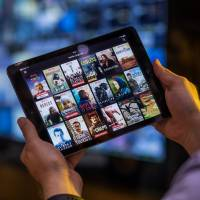 A selection of online video content provided by Netflix Inc. is displayed on an iPad. A Jiji Press survey showed Monday that 15.7 percent of people nationwide subscribe to online video streaming services.   BLOOMBERG