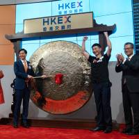 Xiaomi Corp. officials hold a ceremony on July 9 at the Hong Kong Stock Exchange to mark its listing on the bourse. | BLOOMBERG