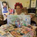 "Animated gifts: Fosse Farmhouse owner Caron Cooper sits at a table surrounded by memorabilia from the anime series ""Kin-iro Mosaic"" in the Costwolds, England."