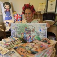 Animated gifts: Fosse Farmhouse owner Caron Cooper sits at a table surrounded by memorabilia from the anime series 'Kin-iro Mosaic' in the Costwolds, England. | KYODO