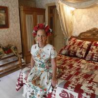 Everything in its right place: Fosse Farmhouse owner Caron Cooper sits on a bed that featured in the anime series 'Kin-iro Mosaic.' After watching the series, Cooper was in awe of the anime's attention to detail in re-creating the B&B. | KYODO