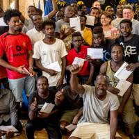 Sudanese migrants arrived in France with the rescue ship Aquarius pose with their refugee identity certificates after a ceremony with the Mayor of Lille Martine Aubry and the Prefect of Hauts-de-France region Michel Lalande on Friday at the City Hall in Llille, northern France. | AFP-JIJI