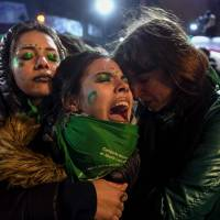 Demonstrators for the legalization of abortion comfort each other outside Congress in Buenos Aires on Thursday after senators rejected the bill. | AFP-JIJI