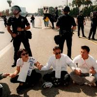 This Oct. 23, 1996, file photo shows UCLA students surrounded by Los Angeles Police officers as they sit on Wilshire Blvd. during an anti-ballot Proposition 209 protest in front of the Federal Building in the Westwood section of Los Angeles. | AP