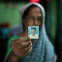 Rina Begum holds a photograph of her son Riazul Islam on July 21. Her son was an alleged drug dealer who was killed by police. | REUTERS