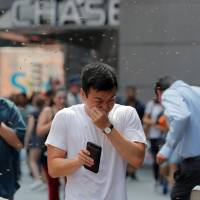 People react to a swarm of bees in Times Square in New York City Tuesday. | BRENDAN MCDERMID / VIA REUTERS