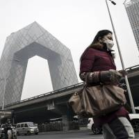 A woman wearing a face mask walks past the China Central Television (CCTV) headquarters building shrouded in haze in Beijing in 2017. Beijing's smog-fighting efforts are seen paying off as the city has experienced its bluest skies in a decade. | QILAI SHEN / VIA BLOOMBERG