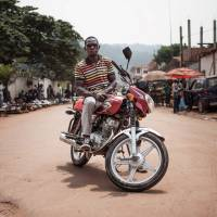 A motorcycle taxi driver, Marcellin, waits for passengers in a street in Bangui on July 21.   AFP-JIJI
