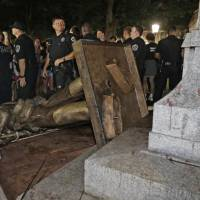 Police stand guard after the confederate statue known as Silent Sam was toppled by protesters on the campus of the University of North Carolina in Chapel Hill, on Aug. 20. | AP