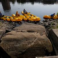 People in canoes visit one of the 'hunger stones' revealed by the low level of water in the Elbe River in Decin, Czech Republic, Wednesday. | DAVID W CERNY / VIA REUTERS