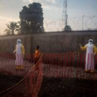 An unconfirmed Ebola patient is led by two medical workers to his new ward in an Ebola Treatment Center (ETC) on Wednesday in Beni, Congo. | AFP-JIJI