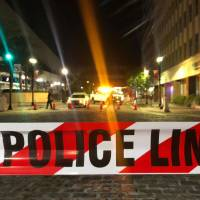 A police car is seen behind police tape blocking a street leading to the Jacksonville Landing area after a shooting in the Florida city Sunday. | AFP-JIJI