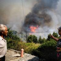 Locals watch the progression of a wildfire close to Monchique, in Algarve, Portugal, Tuesday. Hundreds of Portuguese firefighters and soldiers battled ferocious forest fires that threatened to engulf an Algarve resort town as meteorologists warned of 'significant winds' to come. | AFP-JIJI