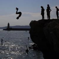 Young men leap off rocks into the ocean at Nice, south-eastern France, on Thursday as heatwave conditions prevail over Europe. | AFP-JIJI