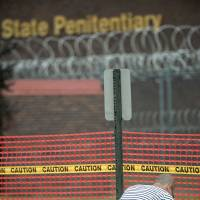 A man, who declined to be identified, kneels outside the Nebraska State Penitentiary Tuesday in Lincoln. | ERIC GREGORY / LINCOLN JOURNAL STAR / VIA AP