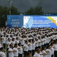 Chinese exercise at Beijing Olympic Park on Wednesday during a National Fitness Day event to herald the Beijing 2022 Winter Olympics. | AP