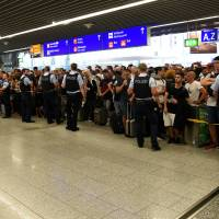 People wait in a terminal during the evacuation of Frankfurt airport in Germany Tuesday. | REUTERS