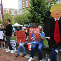 Protesters hold their banners in front of the Alexandria Federal Court in Alexandria, Virginia, Tuesday on day one of Paul Manafort's trial.   AP