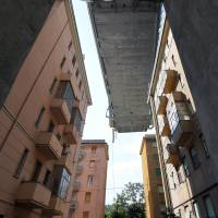 The collapsed Morandi Bridge looms over the restricted 'red zone' of Genoa on Friday. | REUTERS