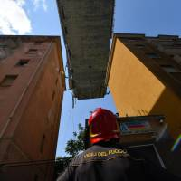 A firefighter looks up at the partially collapsed Morandi highway bridge in Genoa, Italy, on Thursday. | AP