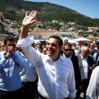 Greek Prime Minister Alexis Tsipras greets supporters on the island of Ithaca, Greece, on Tuesday. | REUTERS