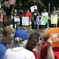 Demonstrators supporting gun law reforms (foreground) walk on the opposite side of the road from counterprotesters supporting Second Amendment rights, near the headquarters of gun manufacturer Smith & Wesson Sunday in Springfield, Massachusetts. | STEVEN SENNE / VIA AP