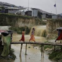 Rohingya refugee girls cross a makeshift bamboo bridge at the Kutupalong refugee camp, where they have been living amid uncertainty over their future after they fled Myanmar to escape violence a year ago, in Bangladesh Tuesday. | ALTAF QADRI / VIA AP