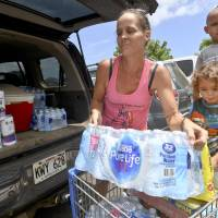 Brianna Sugimura unloads supplies for riding out the storm while her children, Radon-Kai and Kanaloa, watch in the parking lot of a Walmart store Tuesday in Lihue, on the island of Kauai in Hawaii. Hurricane Lane 'is forecast to move dangerously close to the main Hawaiian islands as a hurricane later this week, potentially bringing damaging winds and life-threatening flash flooding from heavy rainfall,' the weather service's Central Pacific Hurricane Center warned as it got closer to the state.   DENNIS FUJIMOTO / THE GARDEN ISLAND / VIA AP