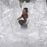 A boy enjoys himself as he cools off in an outdoor water fountain in Seoul on July 24. | AP