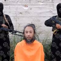 This video image released Tuesday and provided courtesy of SITE Intelligence Group shows Japanese national Yasuda Jumpei appealing for his release as two armed men stand behind him at an unknown location in Syria on the July 25. | SITE INTELLIGENCE GROUP / VIA AFP-JIJI