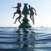 Swimmers jump off a buoy into the Meditteranean Sea at Nice, southeastern France, on Monday as heatwave conditions prevail over Europe. | AFP-JIJI