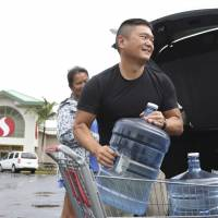 Loren (right) and Ruby Aquino, of Honolulu, load water into their car ahead of Hurricane Lane Wednesday in Honolulu. Hurricane Lane has weakened as it approaches Hawaii but was still expected to pack a wallop, forecasters said Wednesday. | CALEB JONES / VIA AP