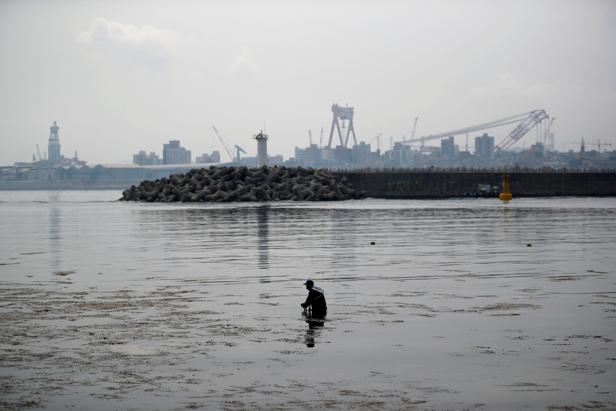 A man wades through the water in front of a Hyundai Heavy Industries shipyard in Ulsan, South Korea, on May 29. | REUTERS