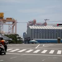A man on a motorbike waits for the traffic lights to change in front of a Hyundai Heavy Industries shipyard in Ulsan, South Korea, on May 29. | REUTERS