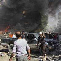Civil Defense workers and Syrian citizens gather after an airstrike hit a market in the Maaret al-Numan area of southern Idlib, Syria, last October. | AP