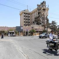 A Syrian rides a motorcycle past the damaged Red Crescent Hospital building in Idlib on Saturday. | AFP-JIJI