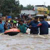 Volunteers and rescue personal evacuate residents of Aluva in the Ernakulam district of India's Kerala state on Friday. | AFP-JIJI
